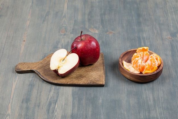 Red apple on wooden board with bowl of tangerine segments