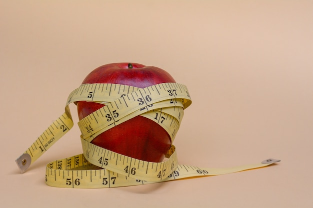 Red apple wrap by measuring tape to measure length on a soft background