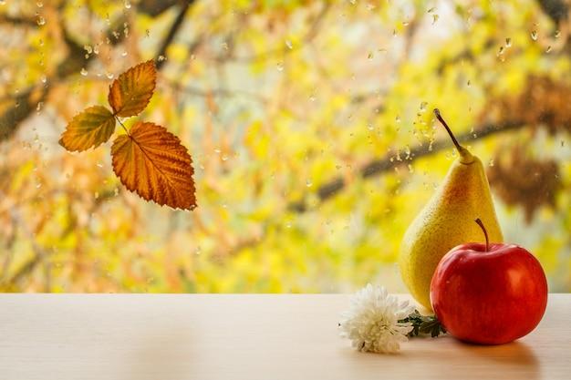 흐릿한 자연 배경에 물방울이 있는 창문 유리에 빨간 사과, 노란 배, 꽃, 마른 잎. 낙엽과 비가 배경에 가을 나무가 있는 창틀에 떨어집니다.