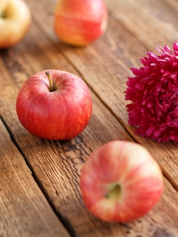 오래 된 나무 판자에 빨간 사과와 애 스 터 꽃. 정원에서 방금 수확한 과일입니다. 필드의 얕은 깊이.