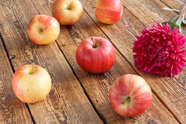오래 된 나무 판자에 빨간 사과와 애 스 터 꽃. 정원에서 방금 수확한 과일입니다.