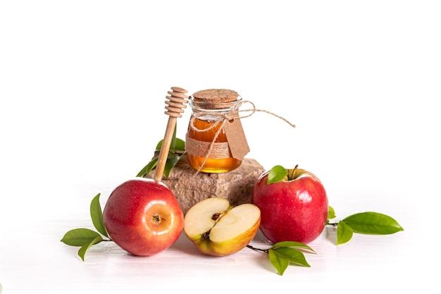 Красные яблоки и мед на белом фоне, традиционная еда еврейского нового года - рош ха-шана.
