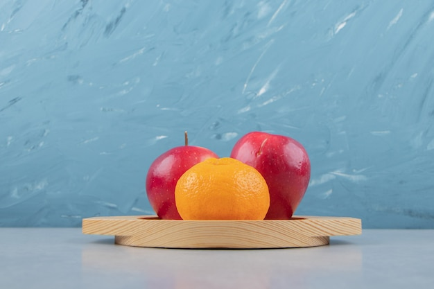 나무 접시에 빨간 사과와 귤