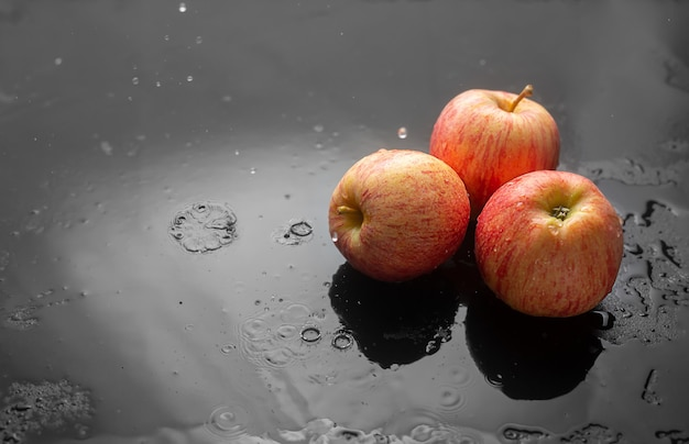Red apples on a dark with raindrops