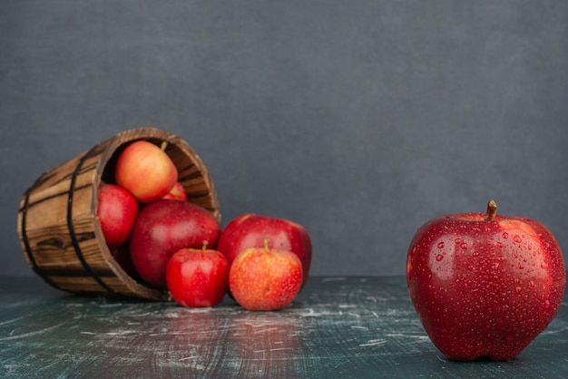 Red apples falling out of bucket on marble table.