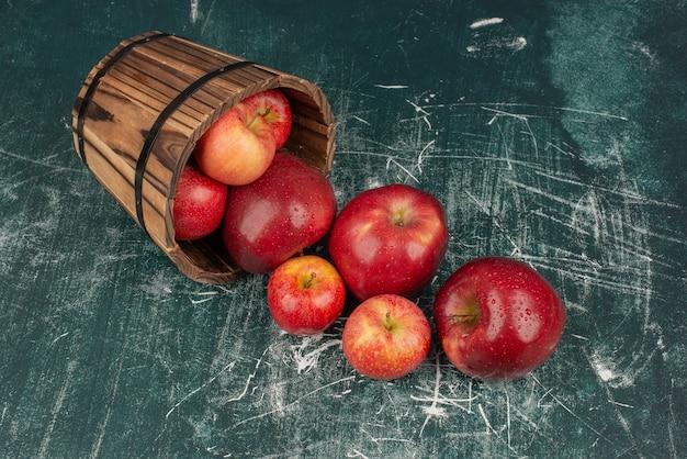 Mele rosse che cadono dal secchio sul tavolo di marmo.