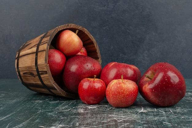 Красные яблоки падают из ведра на мраморный стол