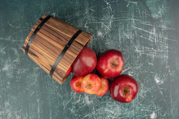 大理石のテーブルのバケツから落ちる赤いリンゴ