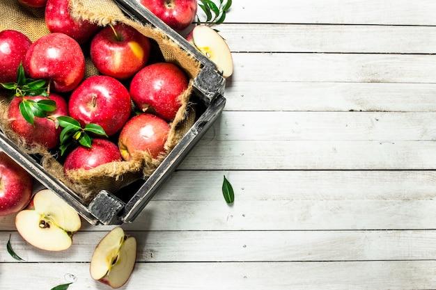 白い木製のテーブルの上の箱の中の赤いリンゴ。
