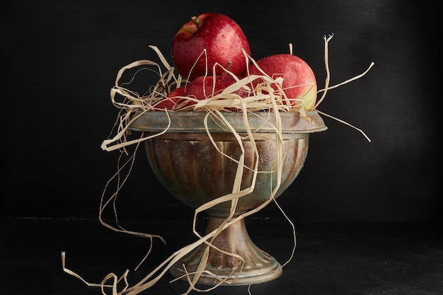 金属製のカップに入った赤いリンゴ。