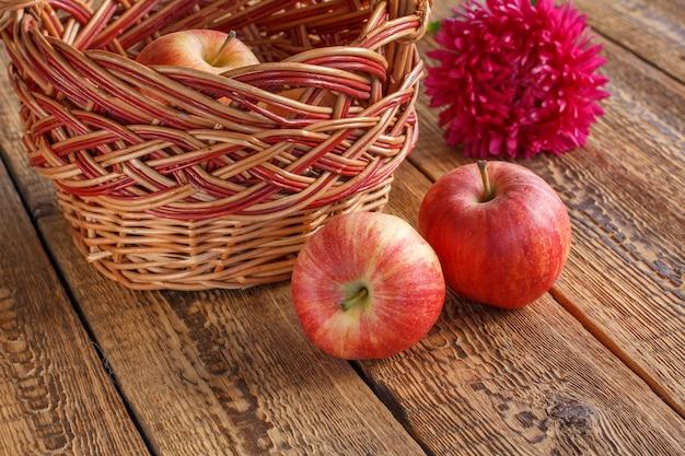 고리 버들 세공 바구니에 빨간 사과와 오래 된 나무 판자에 애 스터 꽃. 방금 수확한 과일입니다.