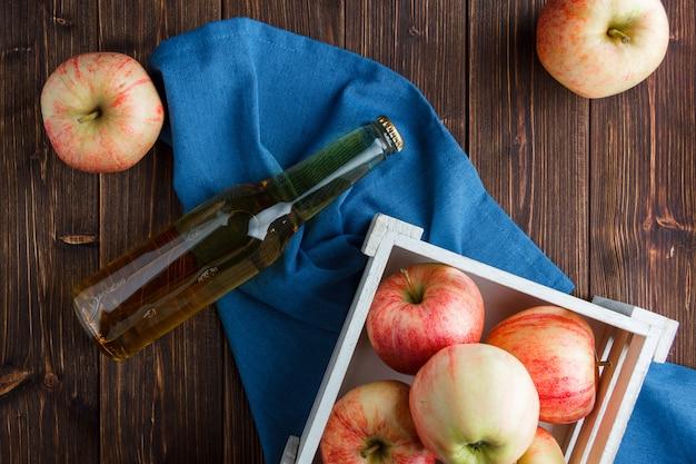 Красные яблоки в деревянной коробке и вокруг с видом сверху яблочного сока на синей ткани и деревянный фон