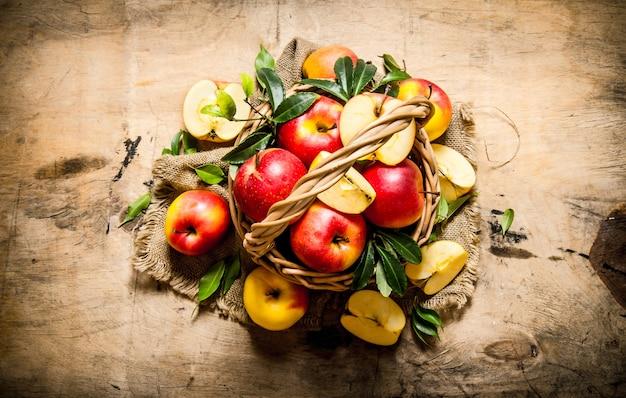 잎을 가진 오래 된 바구니에 빨간 사과. 나무 테이블에. 평면도