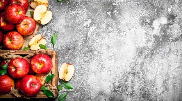 古い箱に入った赤いリンゴ。素朴なテーブルの上。