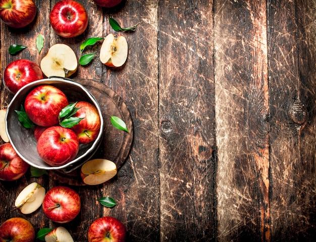 오래 된 양동이에 빨간 사과입니다. 나무 배경.