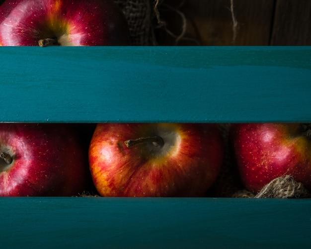 青い木製の箱に赤いリンゴ