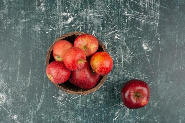 大理石のテーブルの上のバケツの赤いリンゴ。