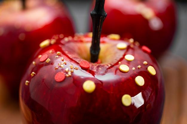 砂糖の装飾が施されたキャラメルの赤いリンゴは、お祝いのハロウィーンのテーブルのオリジナルの御馳走を柔らかくクローズアップします