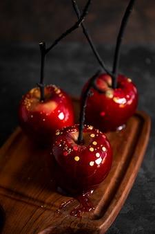 砂糖の装飾が施されたキャラメルの赤いリンゴは、お祝いのハロウィーンテーブルのオリジナルの御馳走です