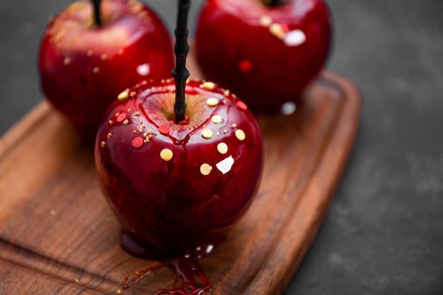 砂糖を添えたキャラメルの赤いリンゴは、お祝いのハロウィーンテーブルのオリジナルの御馳走です
