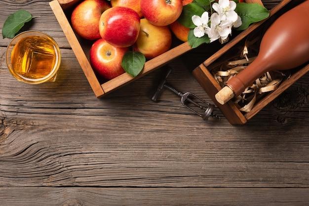 木製のテーブルの上のサイダーの枝、ガラスとボトルと木製の箱の赤いリンゴ。
