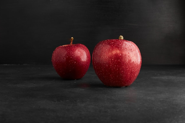 Red apples isolated on black background.