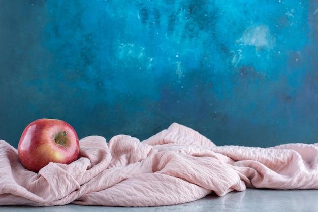 핑크 식탁보에 고립 된 빨간 사과입니다.