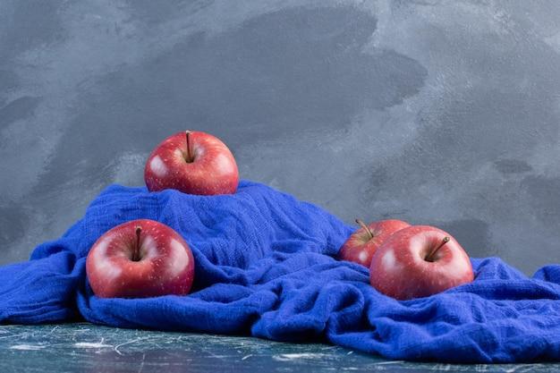 青い表面に分離された赤いリンゴ。