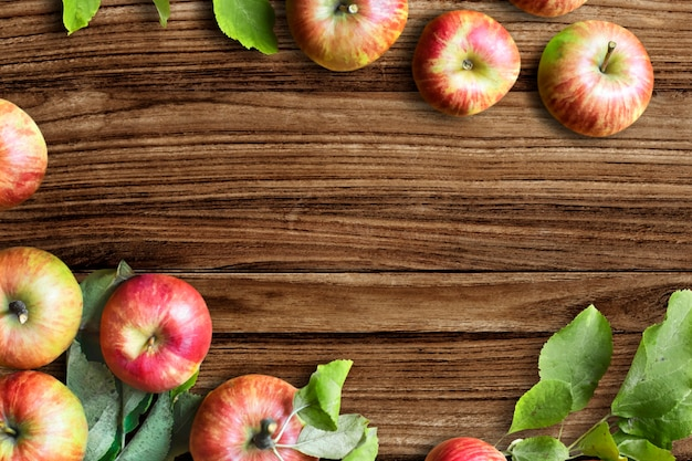 Red apples and leaves flat lay wooden table