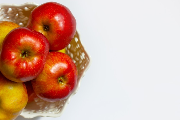 Red apples lie in a beautiful vase on a white background. the concept of healthy eating, proper lifestyle.
