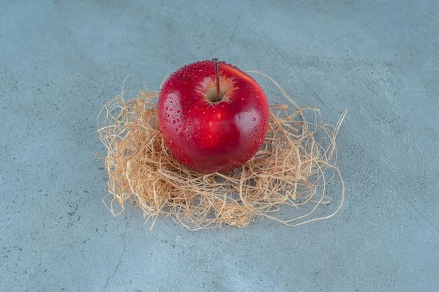 대리석 배경에 마른 짚에 빨간 사과. 고품질 사진
