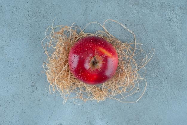 大理石の背景に、乾いたわらの上の赤いリンゴ。高品質の写真