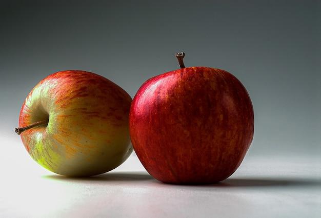 側面に影のある無限の白い背景に赤いリンゴ。