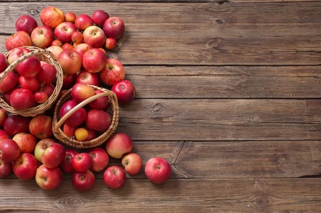 Красные яблоки на старых деревянных фоне
