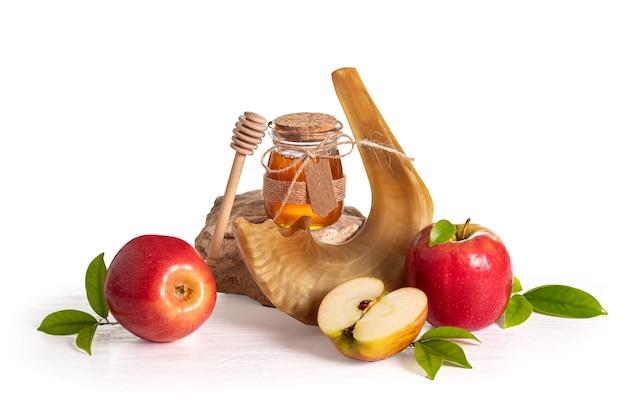 Красные яблоки, шофар, мед на белом фоне, концепция рош ха-шана (еврейский новый год).