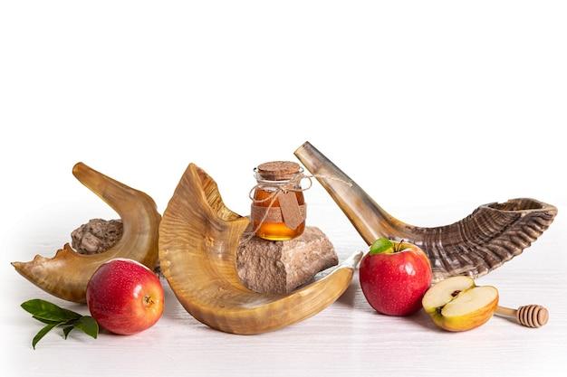 Красные яблоки, шофар (рог), мед на белом фоне, рош ха-шана (праздник еврейского нового года). йом кипур концепция.