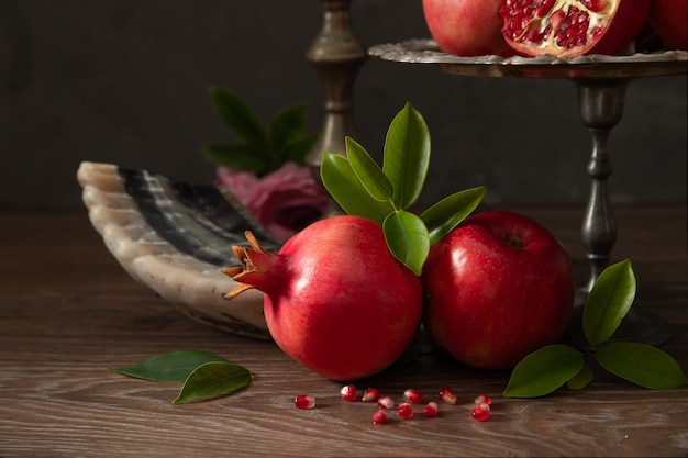Red apples, shofar (horn) and pomegranates on a wooden table, the concept of the jewish new year - rosh hashanah.