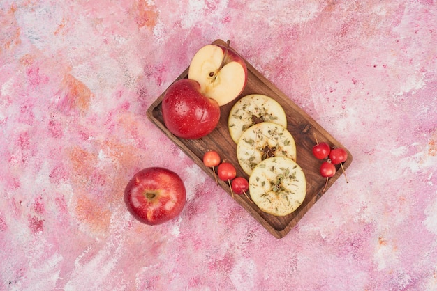 Red apples sliced on wooden board.