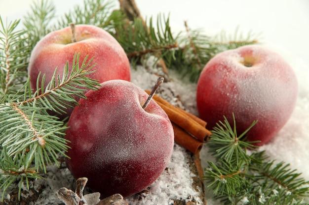 Красные яблоки с еловыми ветками на коре в снегу крупным планом