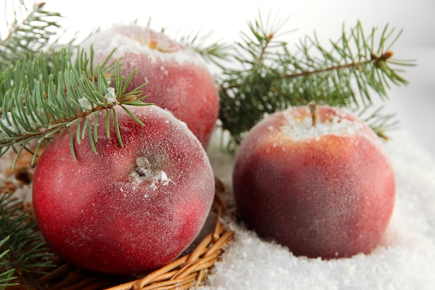 Красные яблоки с еловыми ветками на плетеной подставке на снегу крупным планом