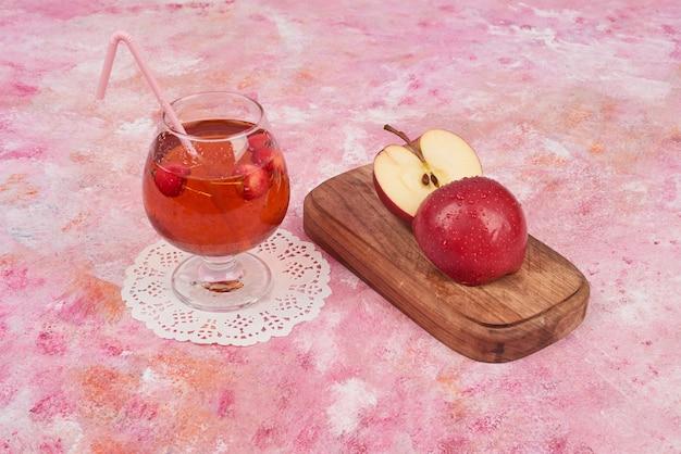 Mele rosse con un bicchiere di succo.