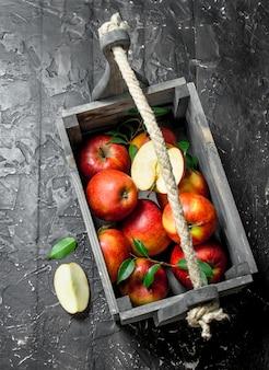 잎과 어두운 시골 풍 테이블에 나무 상자에 사과 슬라이스 빨간 사과.