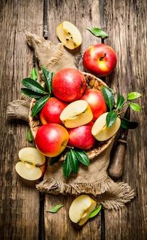ナイフでバスケットに葉を持つ赤いリンゴ。木製の背景に。上面図