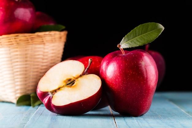 テーブルの上に葉を持つ赤いリンゴ