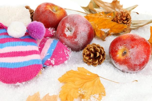 Красные яблоки с варежками в снегу крупным планом