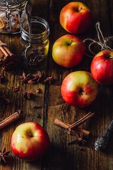 흩어진 정향, 계피 및 아니스 스타와 함께 빨간 사과. mulled 포도주를 준비하기위한 성분. 수직 방향.