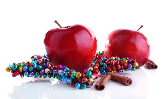 シナモンの棒と白で隔離の装飾的な星と赤いリンゴ
