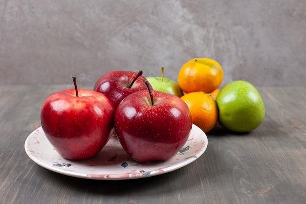 木製のテーブルの上にみかんと赤いリンゴ。高品質の写真