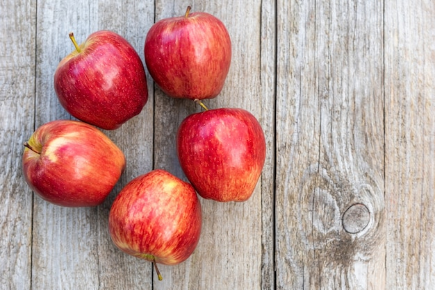 Red apples on a wooden background. copy space.