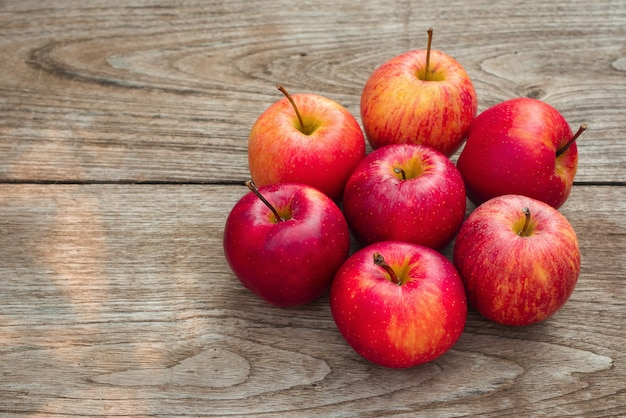 Red apples on a wooden table background